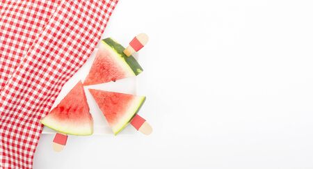 triangle cut, watermelon slice with wooden stick handle and plaid red picnic fabric
