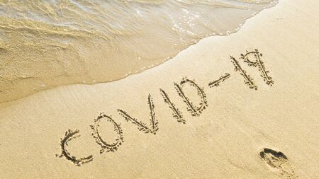 writes covid-19 on the beach. coronavirus measures during the summer holidays