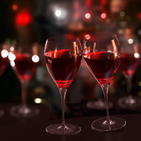 Two glasses of red wine ready for a toast. Blurred background.
