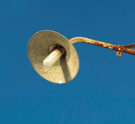 rusty weathered street lamp with energy saving bulb                               photo