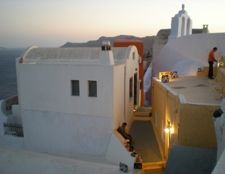 Atmospheric image of an alley in Santorini on sunset time, with street retailers preparing their goods for the evening market photo
