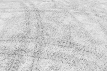 no skid: Background turbulent abstract with blur tire tracks and footstep on the street.