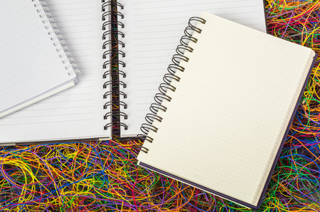 vibrance: Blank spiral notepad notebooks on electric wire.