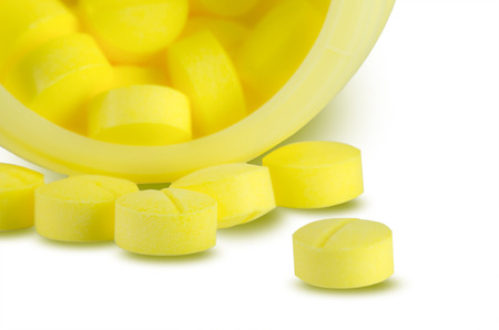 prescribe: Yellow medicine pills and bottle on white background with selective focus.