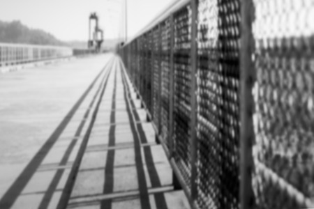 bridged: Abstract with take a look to blur shadow of the steel fence on the dam. Stock Photo