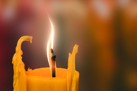 coherence: Candle in front of many defocused candleflames creating a spiritual atmosphere and in remembrance and spirituality.