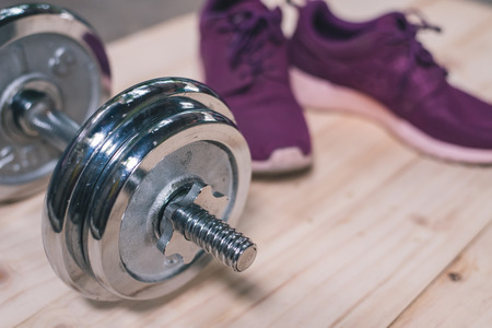 purple shoes: purple sports shoes with dumbell on wooden floor