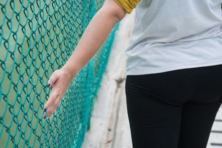 fence wire: Hands touching a metal fence wire