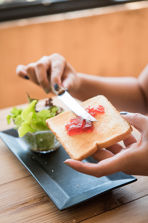 hand jamming: The womans hand is jamming strawberry. Stock Photo