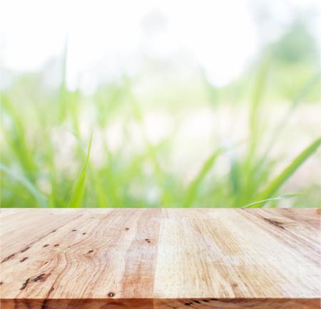 Wood table top on grass blur background Standard-Bild