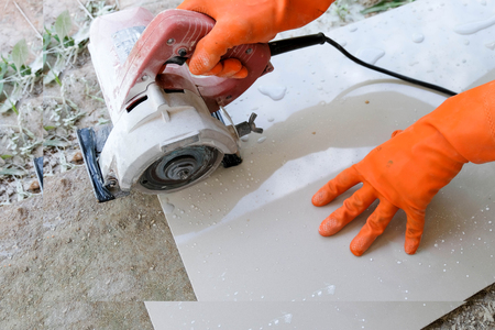 Man with grinder cutting a granito tile