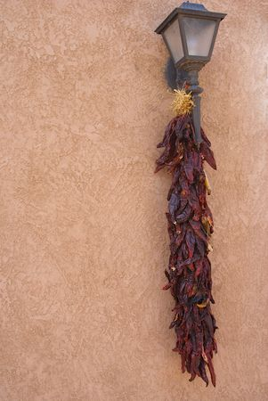 Chiles hanging from a light on a wall Stock Photo