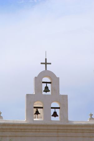 Bells and cross on top of an old Spanish Mission Stock Photo