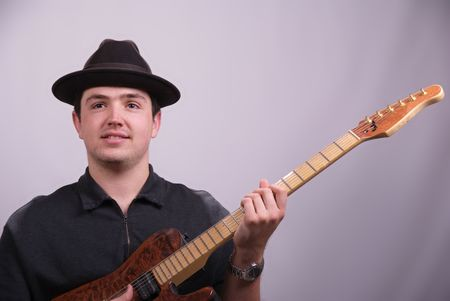 Young man wearing a hat and playing a guitar