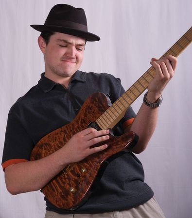 Young man wearing a hat and playing a guitar Stock Photo - 1011046