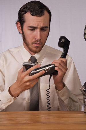 Young businessman dealing with too many phones photo