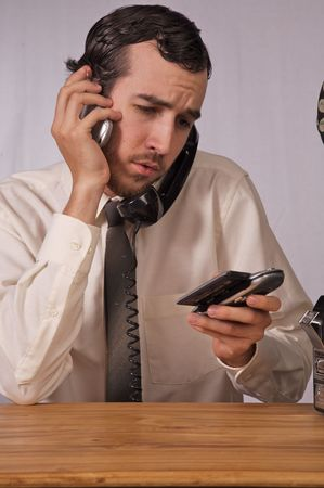 Young businessman dealing with too many phones Stock Photo - 2175989