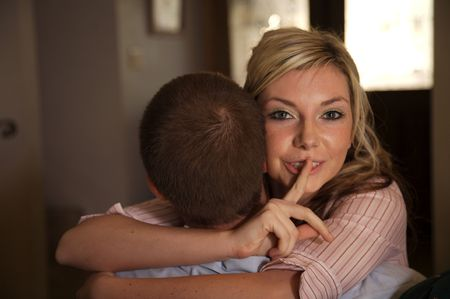 Young woman embracing her lover and indicating it is a secret Stock Photo