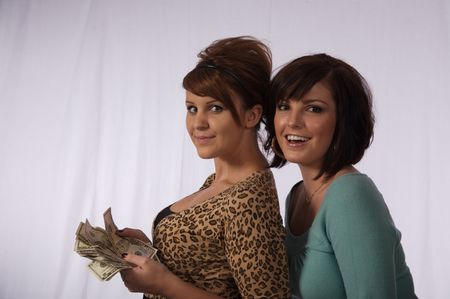 Two young women happy about having money