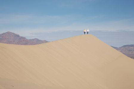 A couple walking along the crest of a dune in Death Valley, CA