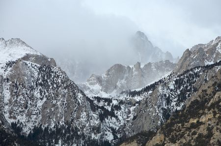 Mt. Whitney shrouded in clouds during winter Stock Photo