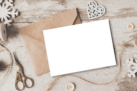 up: Stylish brending mockup to display your artworks. Cute vintage christmas new year gifts mock up on wooden background.