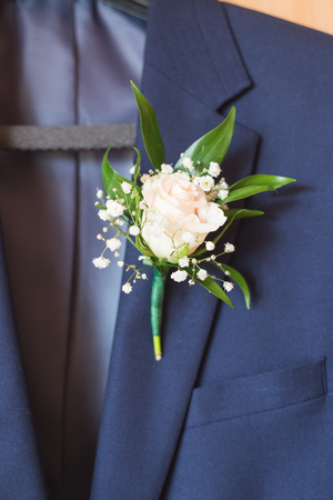 White rose boutonniere pinned to a blue grooms jacket.