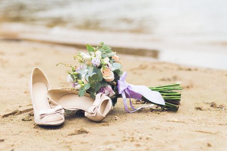 Beautiful boho rustic composition with a bridal bouquet and wedding shoes standing on a beach sand Foto de archivo