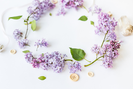 Flat lay top view photo of spring composition. Wreath made of lilac flowers on white background. Summery floral frame.