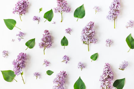 Flat lay top view photo of a pattern made of a lilac flowers, leaves and petals. Naturals rustic spring photography.