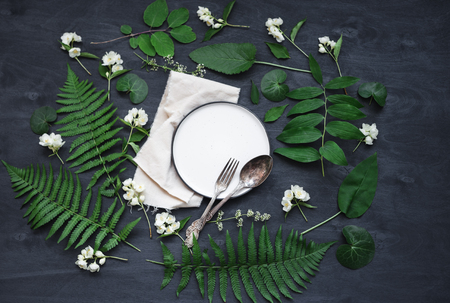 Beautiful boho spring table set up mockup with wild flower and plant decoration. Trendy flat lay top view photo.