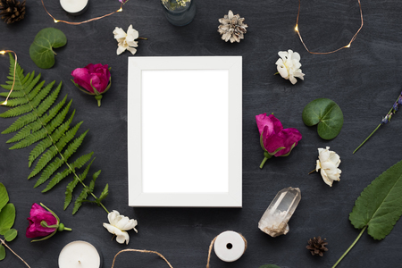 Flat lay top view mockup of a frame on a black background with wild flowers. Beautiful trendy layout photo.