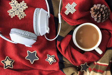 christmas concept. cup of coffee and white headphone on red sweater background. over light Imagens