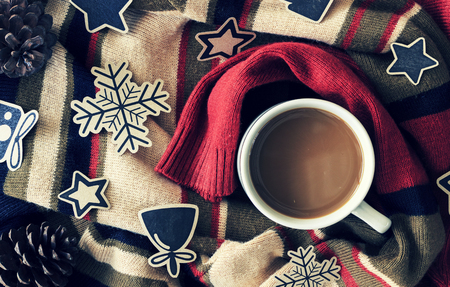 christmas concept. cup of coffee on red sweater background. over light and vintage tone