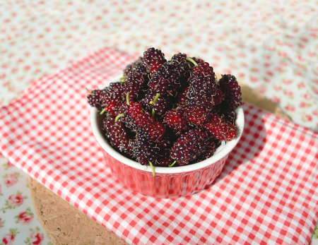 Fresh mulberries in a red bowl Stock Photo