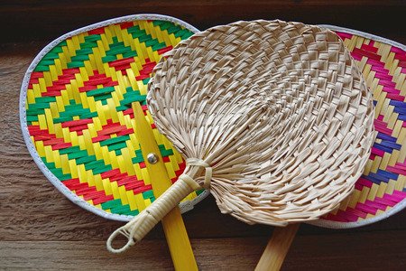 Collection of colourful handmade Thai native fan on wood