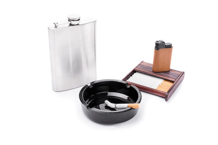 Flask, ashtray, some cigarettes and lighter on a cigarette case isolated on white background photo