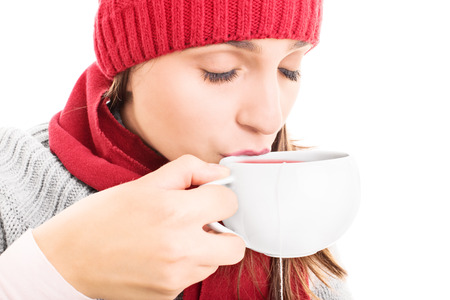 Close-up shot of a young girl wearing winter clothes and drinking a hot cup of tea, isolated on white background photo