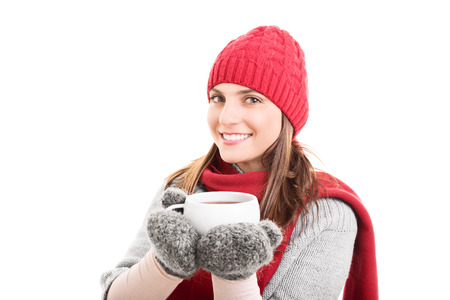 Beautiful girl in winter clothes holding a hot cup of tea isolated on white background photo