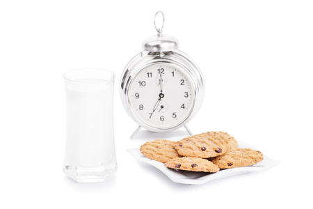 seven o'clock: Milk and cookies with a clock isolated on white background
