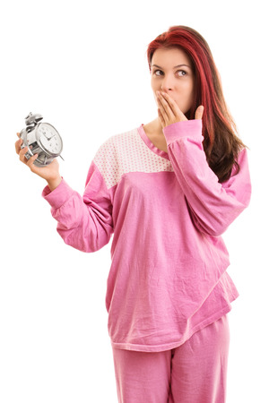 overslept: Oooh, overslept, again hihi. Young girl in pyjamas holding an slarm clock isolated on white background Stock Photo