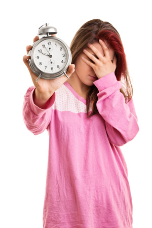dissapointed: Oh my, there goes my timing of things. Young girl in pyjamas holding an alarm clock isolated on white background Stock Photo