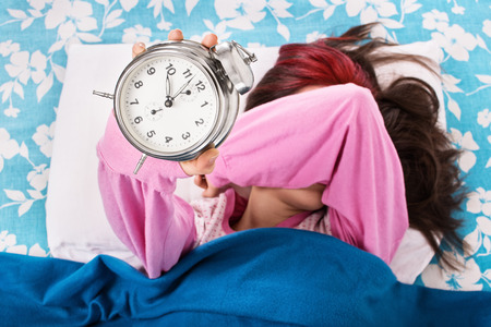 overslept: Oh now youre really gonna stop ringing. Young girl throwing the alarm clock.