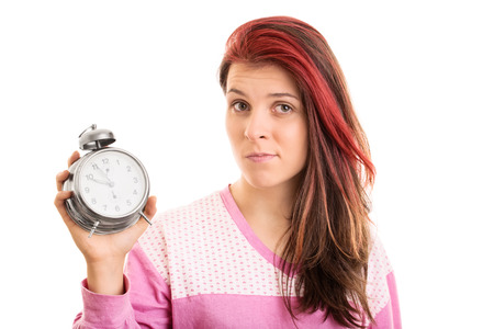 overslept: There, I overslept again. What can I do? Young girl in pyjamas holding an alarm clock isolated on white background Stock Photo
