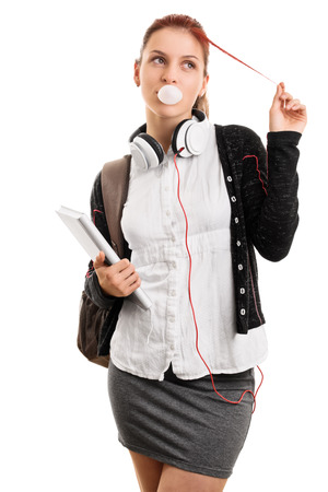 bubble gum: Highschool lifestyle. Young girl with books and backpack making bubble gum bubbles isolated on white background