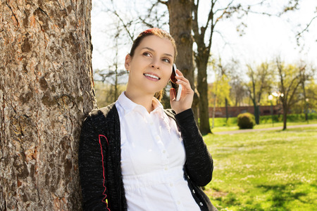 my dear: Im very glad i heard you. Young girl in park talking on the phone with a dear person. Stock Photo