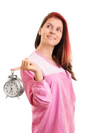 obligations: Wake up, its a beautiful day. Smiling young girl in pyjamas holding an alarm clock, isolated on white background Stock Photo