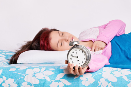 no rush: Mmm, one more minute please... Young girl overslept with alarm clock in her hand Stock Photo
