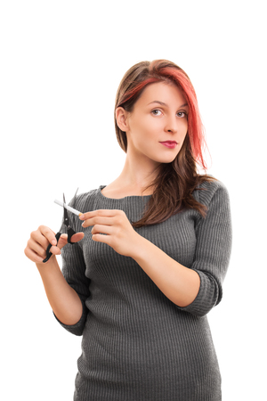 bad habit: Cut it out with this bad habit! Young girl cutting a cigarette with scissors isolated on white background