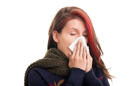 cold season: Cold and flu season. Portrait of a girl in winter clothes blowing her nose, isolated on white background. Stock Photo